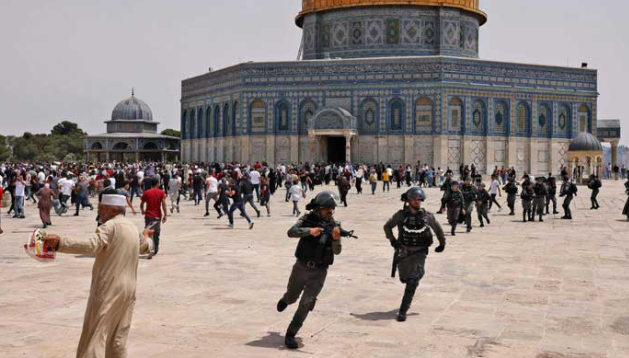 Worshipers rushing to safety as Israeli police forces storm the Al Aqsa mosque compound, hours after truce was announced between Israel and Hamas, on May 21, 2021. — AFP